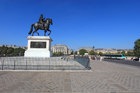 right bank: PARIS, FRANCE - SEPTEMBER 10 2014: Pedestrians by a bronze statue of Henry IV on Pont Neuf towards the right bank of the Seine. This equestrian statue is where the bridge spans the Ile de la Cite.