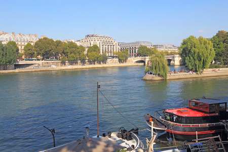 rentals: PARIS, FRANCE - SEPTEMBER 10 2014: Barges and houseboats near Pont Neuf and the Ile de la Cite on the left bank of the river Seine. Many of these boats are popular tourist rentals during the summer.
