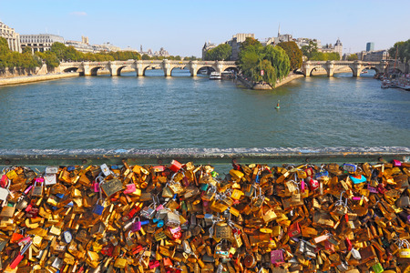 keylock: Love locks on the Pont des Artes in Paris, France with the Pont Neuf and Ile de la Cite in the background