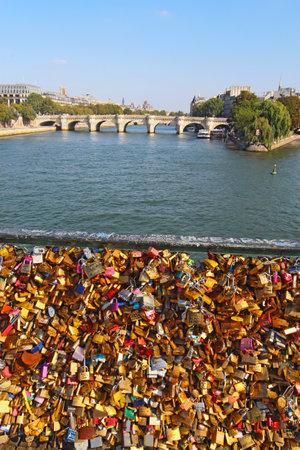 ile de la cite: Love locks on the Pont des Artes in Paris, France with the Pont Neuf and Ile de la Cite in the background vertical
