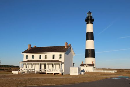 obx: The Bodie Island lighthouse and keepers quarters at the Cape Hatteras National Seashore against a bright blue sky