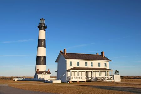 The Bodie Island lighthouse and keepers quarters at the Cape Hatteras National Seashore against a bright blue sky