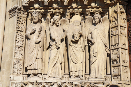 cathedrale: Statues to the left side of the Portal of the Virgin on the west facade of the Cathedral Notre Dame de Paris, France, including Saint Denis holding his head