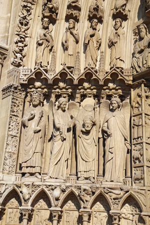 heads old building facade: Statues to the left side of the Portal of the Virgin on the west facade of the Cathedral Notre Dame de Paris, France, including Saint Denis holding his head