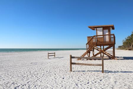 ブレーデントン、フロリダ州近くアンナマリア島の貝殻石灰岩ビーチの白い砂の上のイス