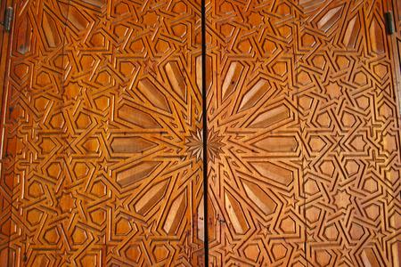 フェズ、モロッコのフェズエルバリ メディナ イナニア マドラサで刻まれた杉の華やかなドアのクローズ アップの詳細