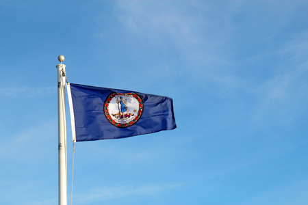 Flag of the Commonwealth of Virginia flying from a while pole against a bright blue sky and cirrus clouds background