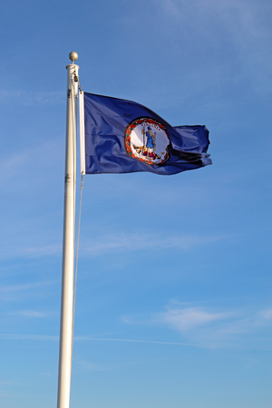 Flag of the Commonwealth of Virginia flying from a while pole against a bright blue sky and cirrus clouds background vertical