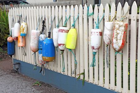 Several types and shapes of marine buoys hanging from a white picket fence near the California coast