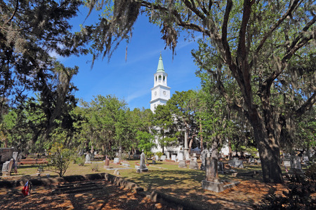 Spire and graveyard framed by Spanish moss-covered trees at the parish church of St. Helena in the historic district of downtown Beaufort, South Carolina Stock Photo