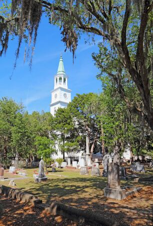 Spire and graveyard framed by Spanish moss-covered trees at the parish church of St. Helena in the historic district of downtown Beaufort, South Carolina vertical