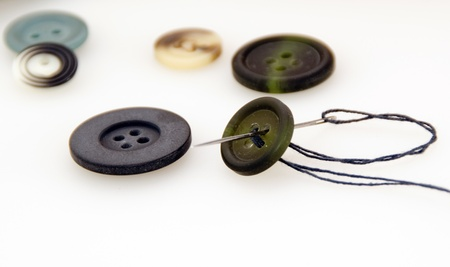 Sew a button with a needle and thread