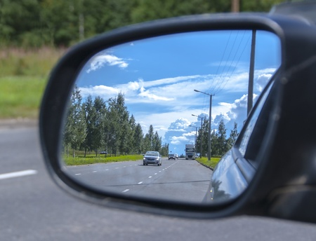 The reflection of cars in side mirror of car