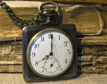 Retro pocket watch and tattered folios Stock Photo