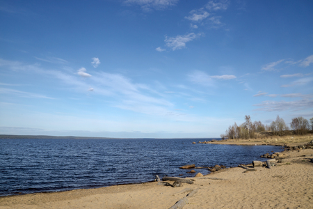 Sandy beach on lake in sunny spring day
