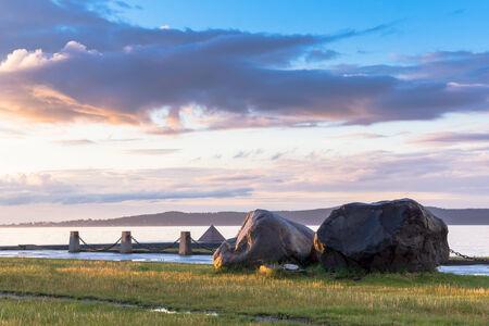 La puesta del sol del verano en el cielo nublado en el lago muelle Foto de archivo