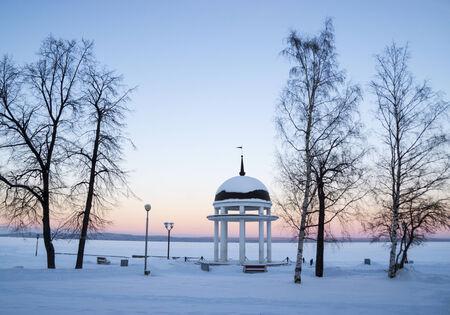 Rotonda en el lago de invierno en la puesta del sol