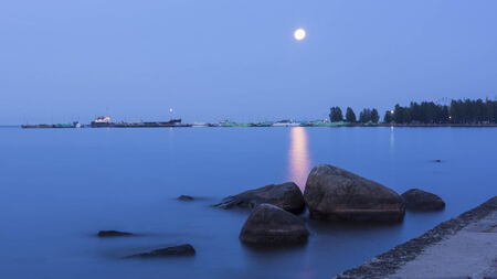 Full moon at white nights season above lake in Karelia