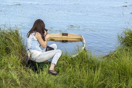 Young slender woman on lake in summer