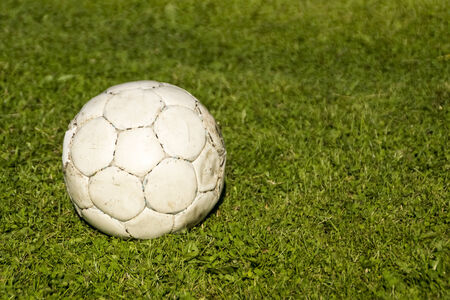 Old shabby ball on green grass