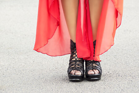 Slender woman legs on heels and red dress in summer