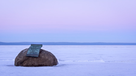 Memorial plaque on boulder on lake shore in winter