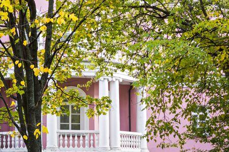 autumn garden: White balcony of pink house of classic style in autumn garden Stock Photo