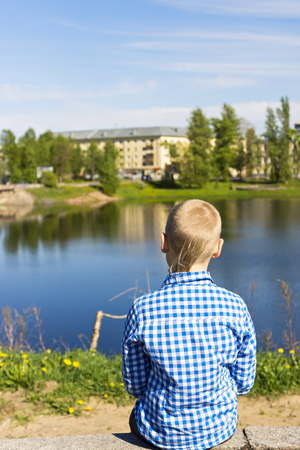 Ten year boy looks on city from river shore Stock Photo