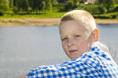 sunspot: Portrait of boy on summer river background