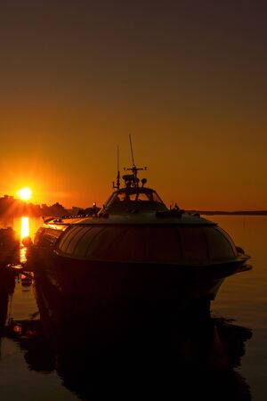 Silhouette of ship in city port on sunset Stock Photo