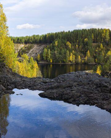 Wild pond on rock in forest in autumn Foto de archivo