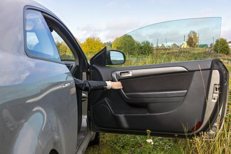 car door: Human hand opens the car door In the countryside