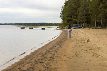 goes: Girl goes on coast of lakeside in taiga