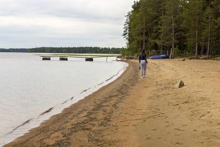 La muchacha va en la costa del lago en la taiga Foto de archivo