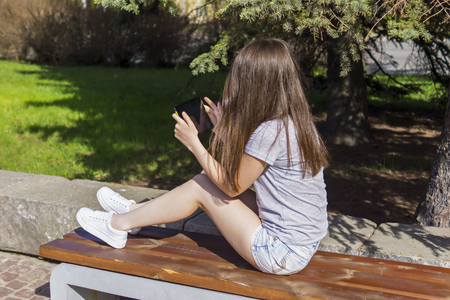 haired: Long haired girl enjoys the tablet on bench Stock Photo