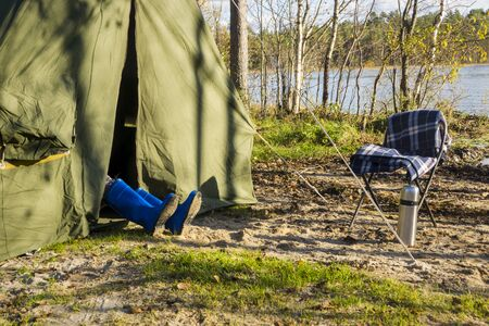 oldschool: Legs in gumboots sticking out of tent