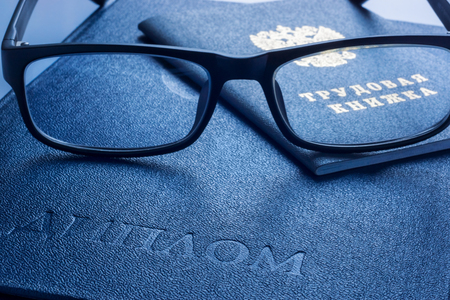 Glasses on diploma of higher education and employment history book Stock Photo