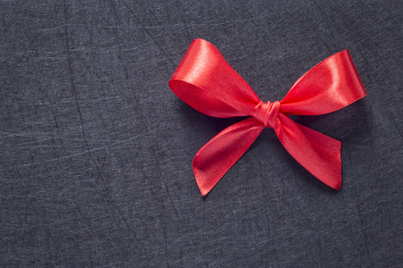 Red bow on black textured background