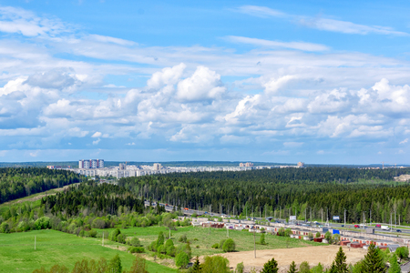 Highway and city in northern forest in summer