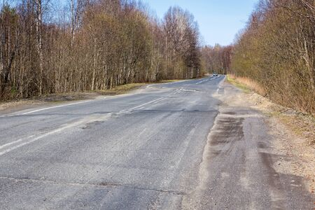 Broken out-of-town asphalt road Stock Photo