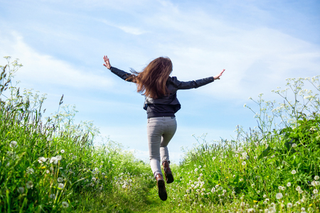 Happy girl running through summer meadow towards the nature
