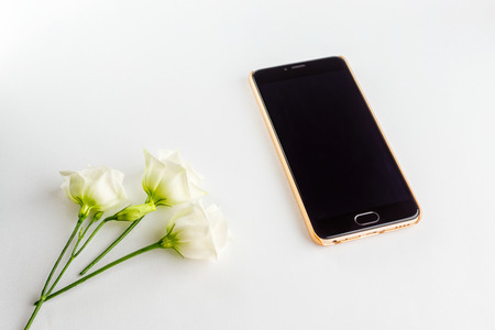 Delicate white flowers and modern powerful smartphone