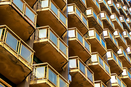 Geometric background of high-rise building wall with many balconies