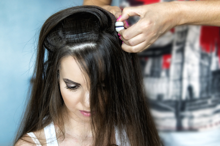 Hairdresser does the hairstyle for brunette girl