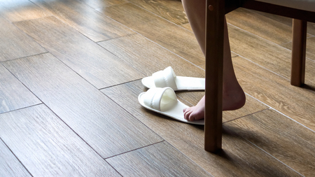 Barefoot female foot and white slippers on floor
