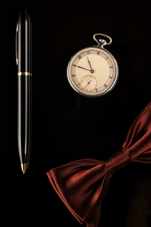 Pocket watch, pen and bow-tie are mens accessories