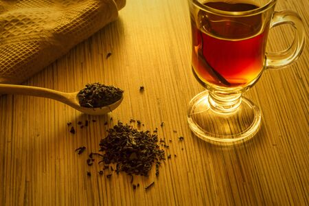 Brewing tea, spoon with tea leaves and cup of tea Stock Photo
