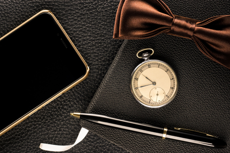 Mens accessories are watch, pen, phone and bow-tie