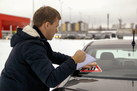 Man pastes thorn sign sticker on car window Stock Photo