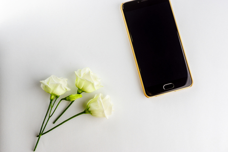 Small flowers and modern stylish smartphone